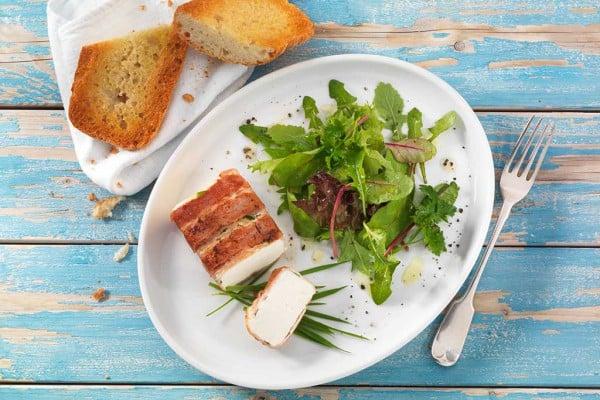 Gebackener Fetakäse mit Bacon und Weizengras an knusprigem Baguette