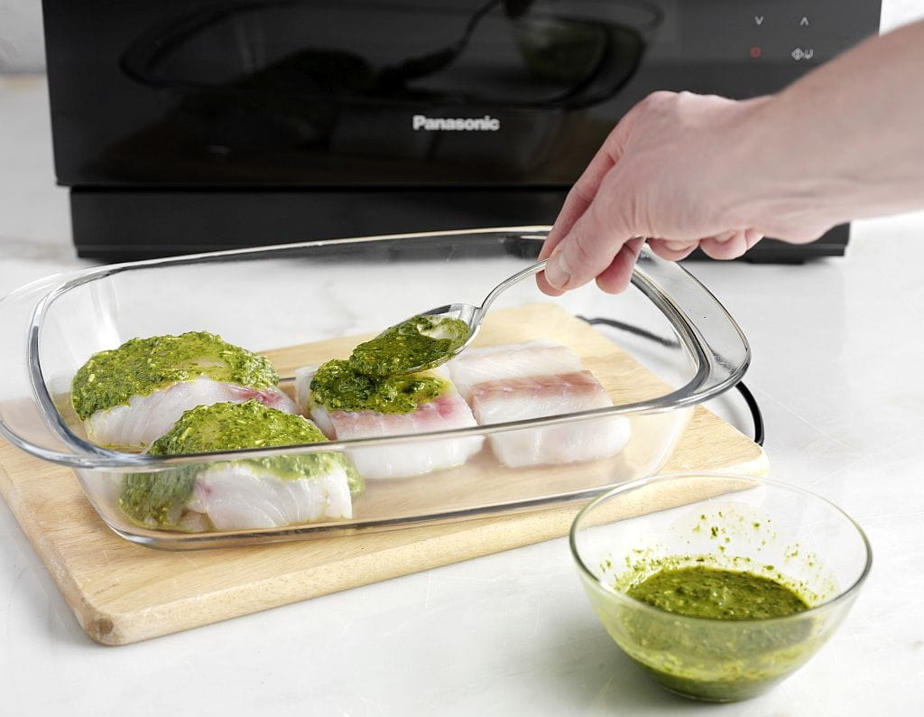Pesto-Marinade auf den Fischfilets verteilen.